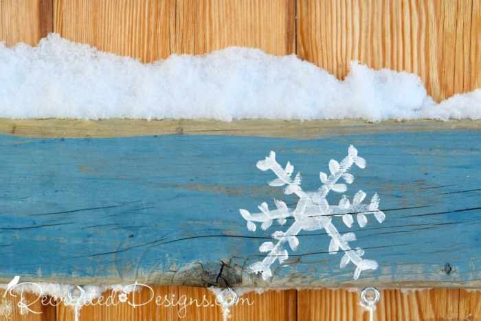 snowflake painted on reclaimed wood and snow