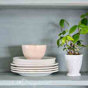 white ironstone dishes with a small plant on a Farmhouse hutch