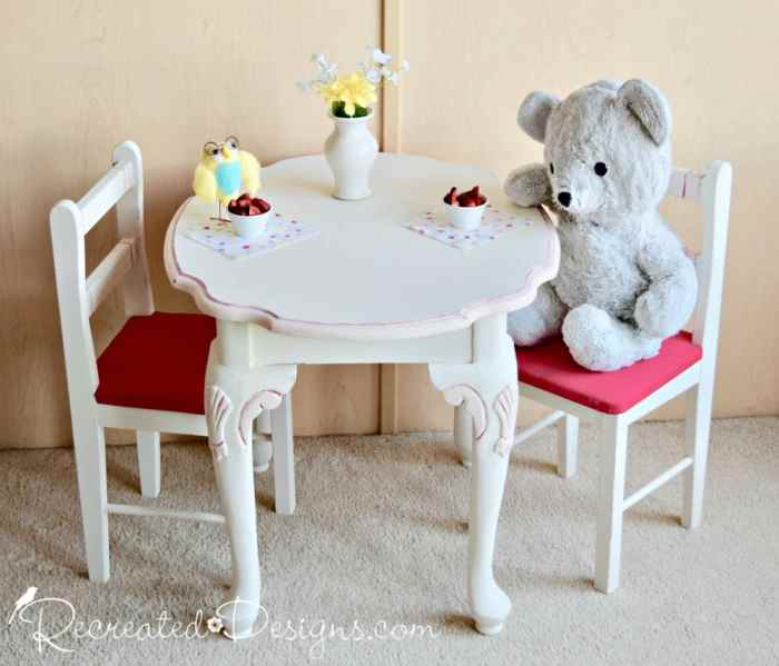 an upcycled side table and child's chairs are turned into a play set for a tea party