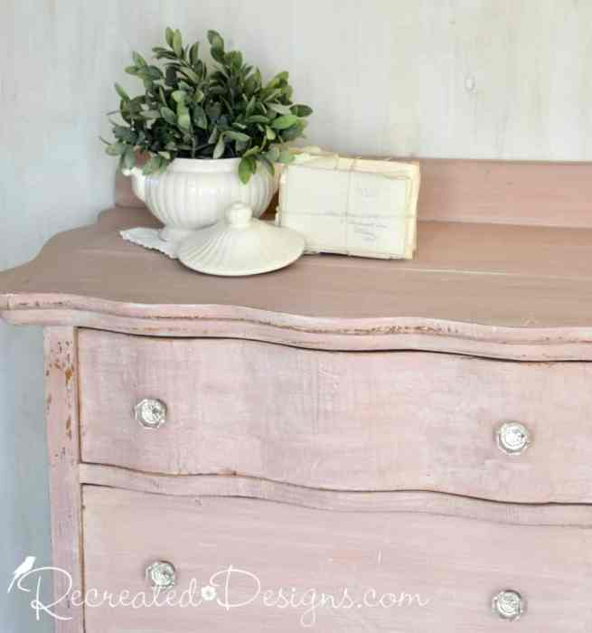 vintage ironstone and an old stack of letter on a pink milk painted dresser