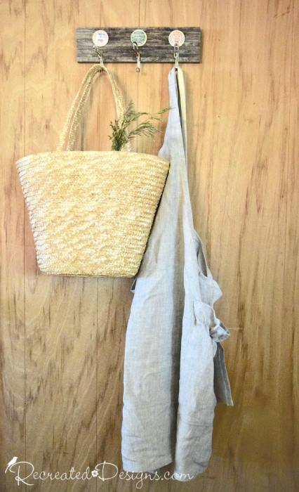 linen apron hanging from an upcycled piece of wood and vintage milk caps