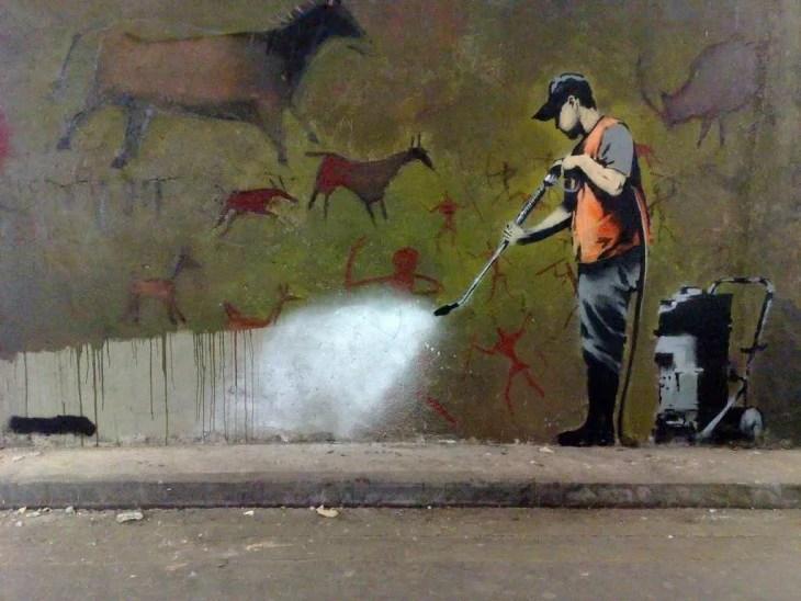 Grafiti de Bansky donde una persona esta aspirando pinturas rupestres de la pared