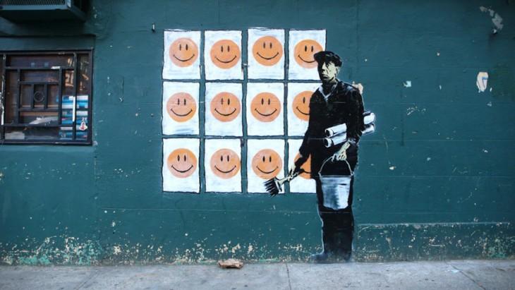 Grafiti de Bansky con un hombre con muchos cuadros de sonrisas