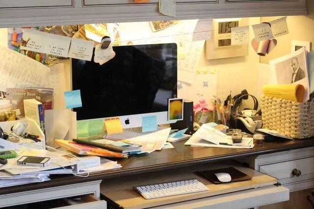 escritorio con una computadora lleno de papeles y notas pegadas en la pared