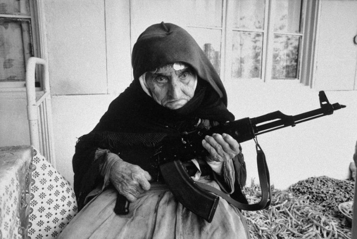 mujer anciana sosteniendo un rifle mientras esta sentada en la cama de su casa