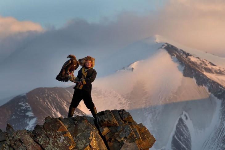 niña de 13 años sujetando una águila en la punta de una montaña de mongolia