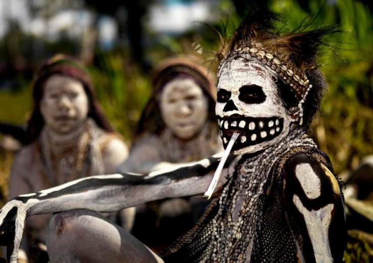 mujer pintada de blanco y negro por todo el cuerpo en medio de un ritual en nueva guinea
