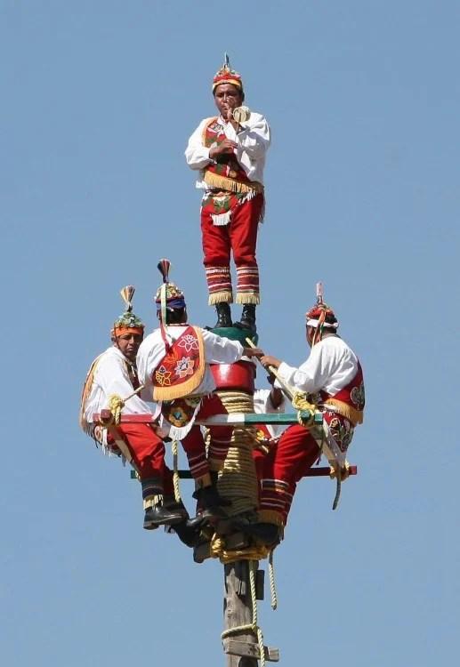 hombres de México con trajes típicos al subir para volar desde un mastil