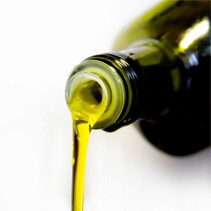 Botella verde vertiendo aceite de oliva