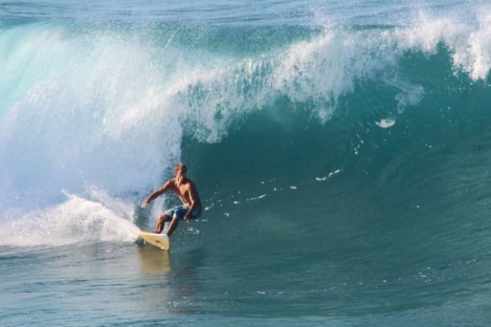 Chico practicando surf en la costa norte de República Dominicana