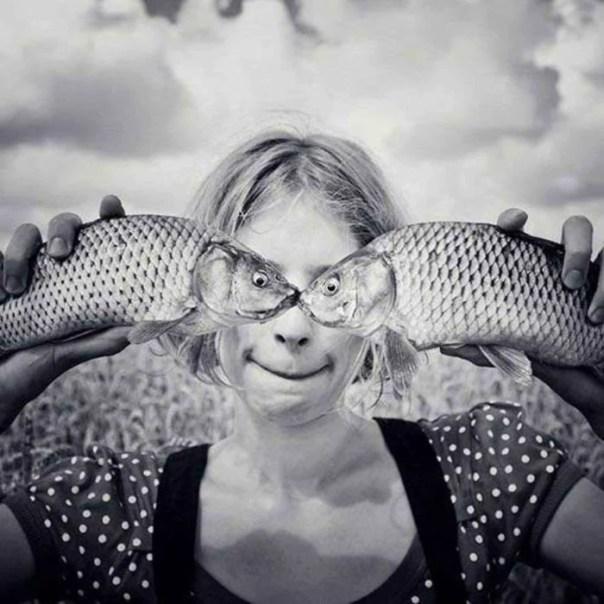 Mujer sosteniendo dos pescados de perfil haciendo la ilusión de que los ojos de los pescados son de ella