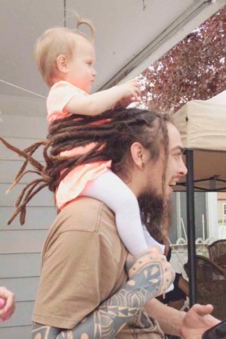 hombre sostiene a bebé con sus rastas