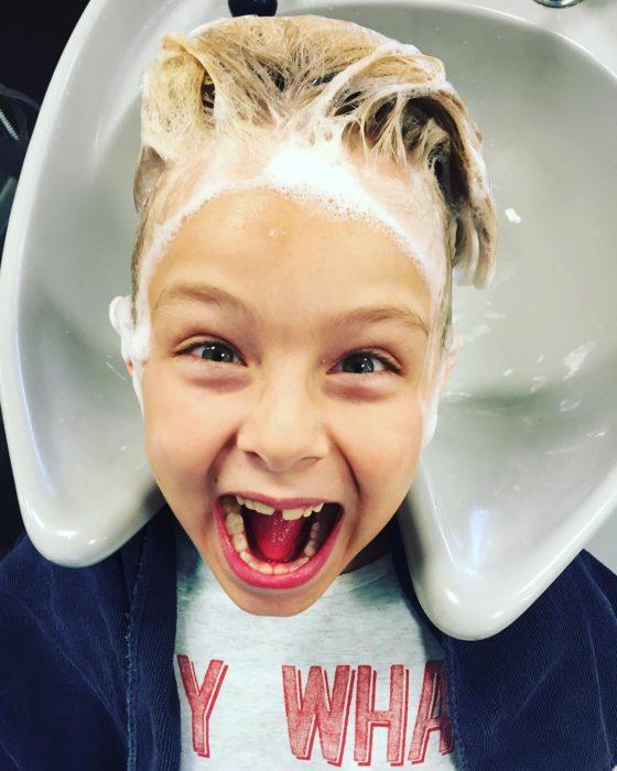 niño sonriendo con champú en el pelo