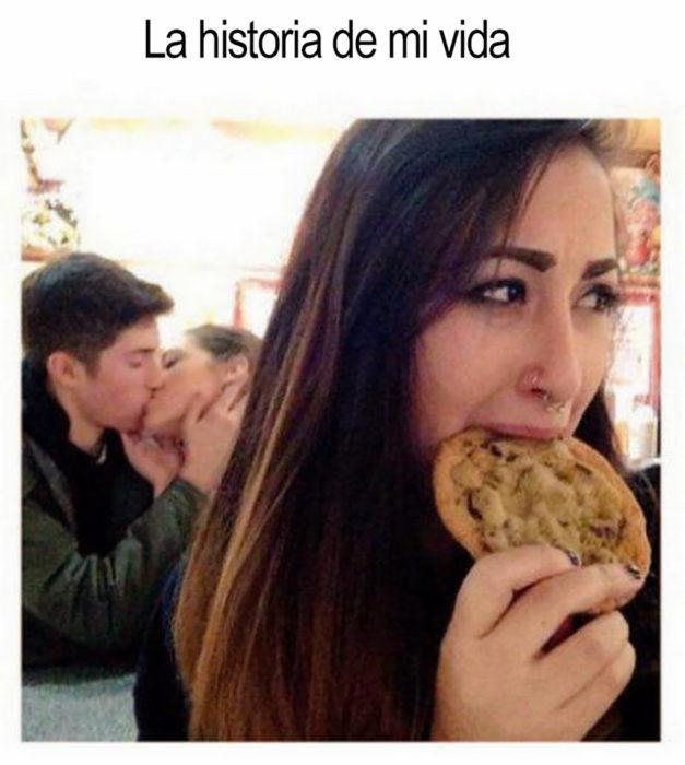pareja besándose y adelante una chavala comiendo una galleta