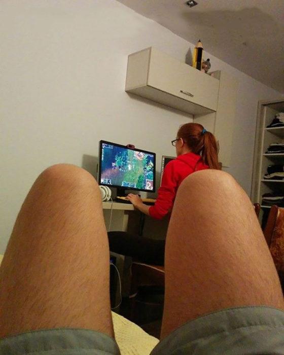 mujer jugando vídeojuegos mientras su novio enseña las piernas