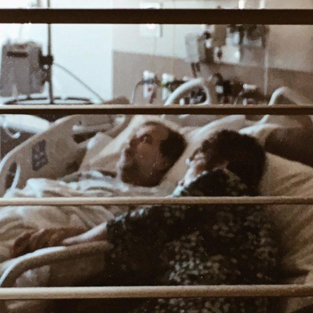 hombre en cama de hospital y mujer a su lado