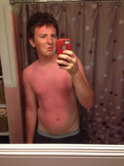 chico quemado por el sol tomándose una fotografía en el espejo