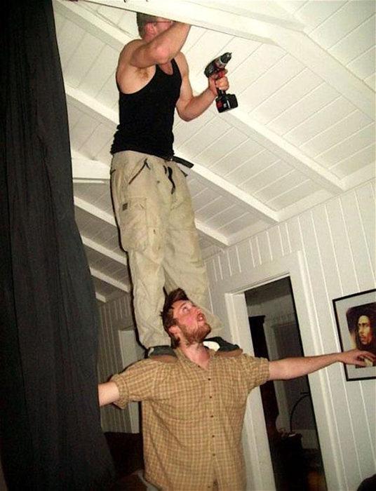 hombre taladrando encima de otro hombre