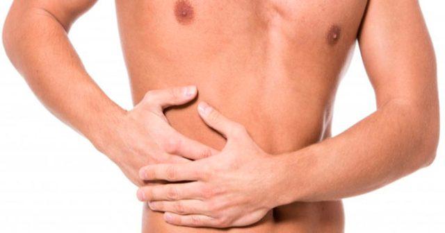 hombre tocándose un costado del abdomen