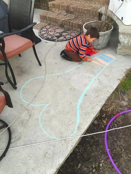 niño dibuja un corazón en el suelo que semeja un símbolo fálico