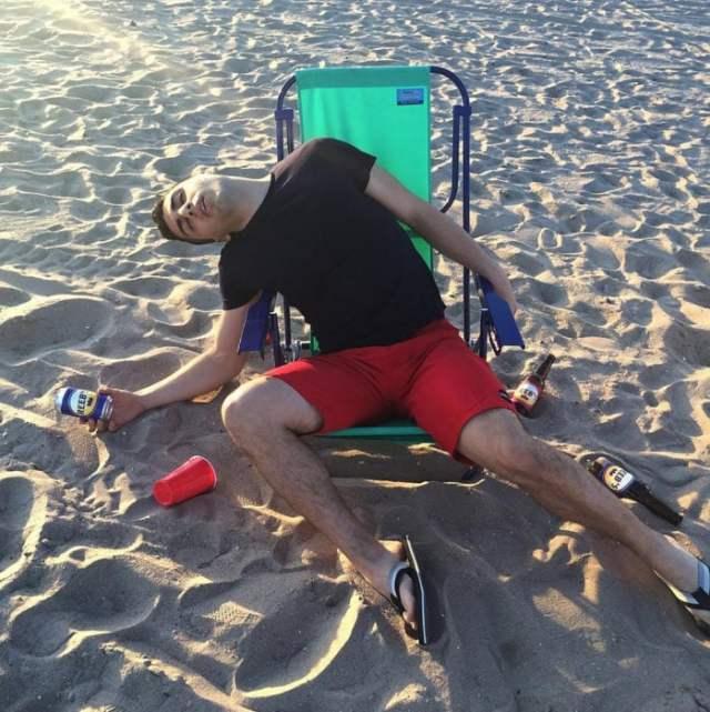 borracho sentado en la playa