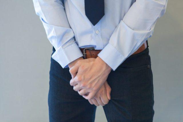 hombre vestido formalmente tocándose la entrepierna