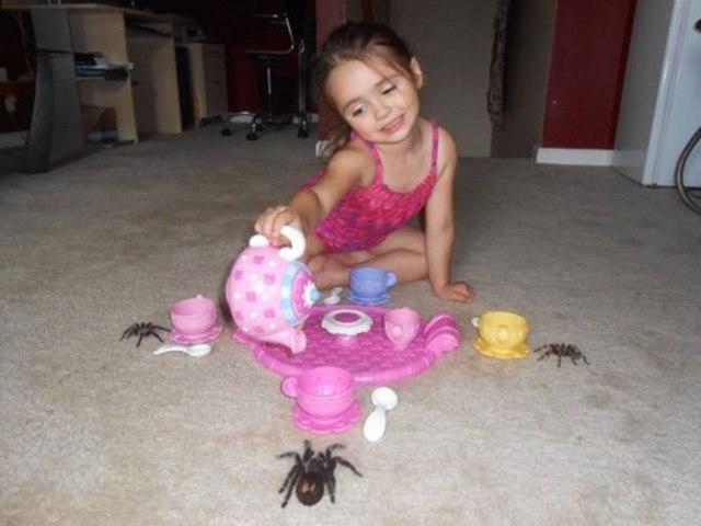 niña bebiendo el té con tres tarántulas