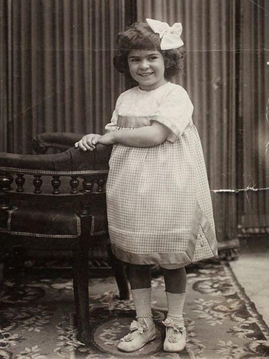 Frida Kahlo de niña parada con vestidito blanco