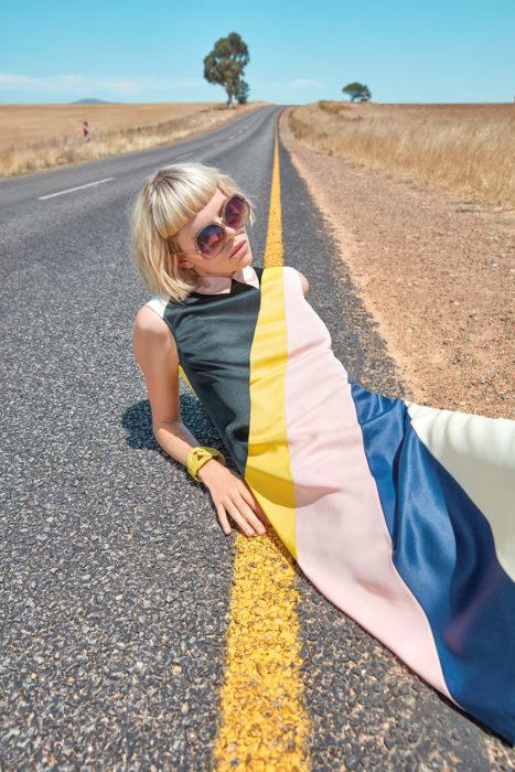 chica con vestido a rayas recostada en carretera