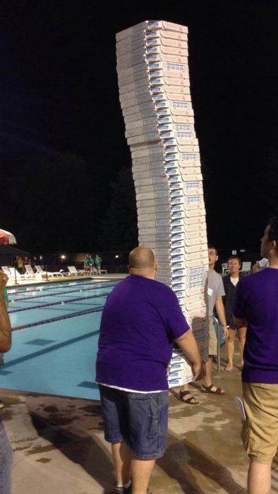 Hombre cargando muchísimas cajas de pizza