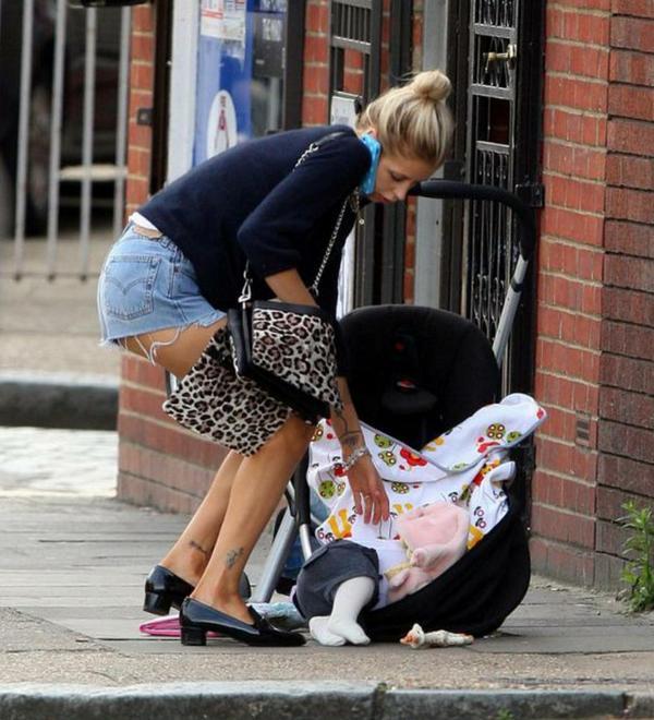 Mujer procura recoger a su bebé del apartamento con el celular en el oído