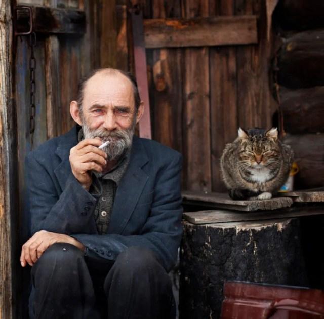 anciano fumando con su gato