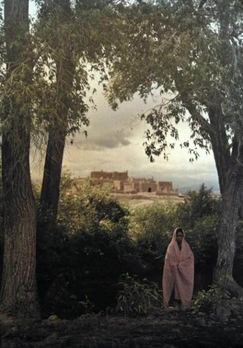 fotografía vieja de mujer posando a las afueras de su pueblo
