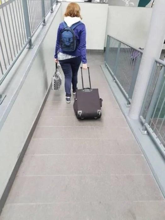 mujer transportando maleta de forma incorrecta