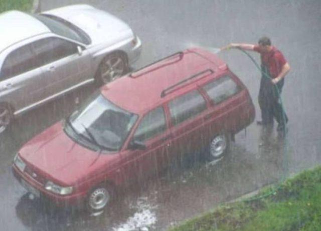 hombre lavando su carro durante la lluvía