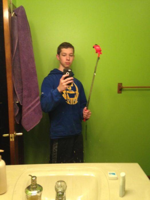chico bebiendo selfie con su stick de forma incorrecta
