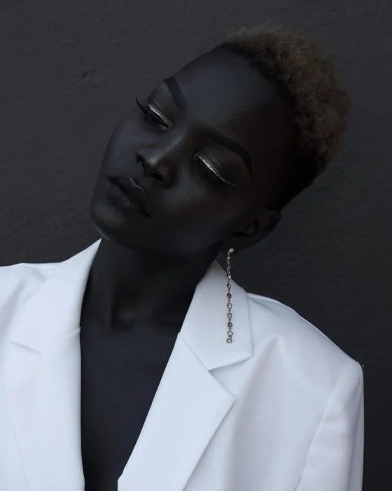 Hermosa modelo negra con traje blanco