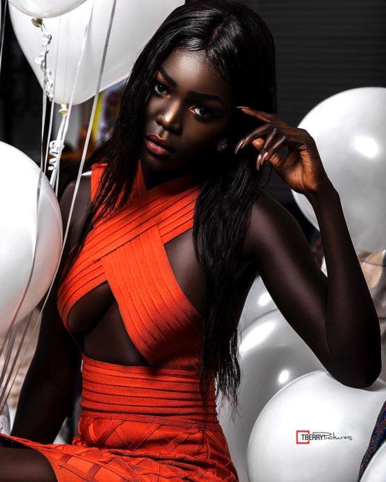 Modelo negra con vestido naranja y globos blancos alrededor