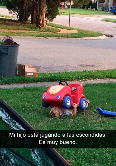 Niño debajo de su vehículo de juguete