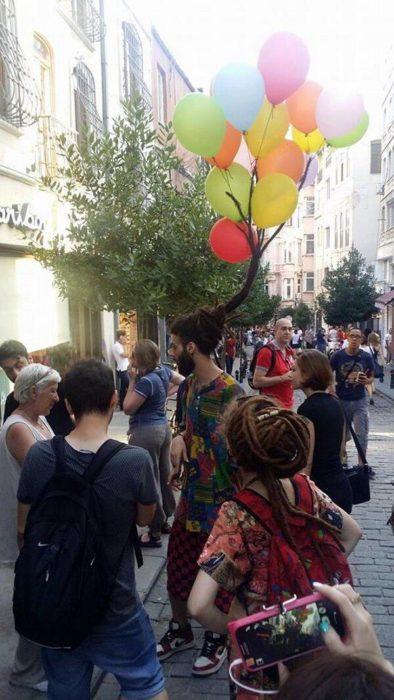 hombre con globos con helio en el cabello