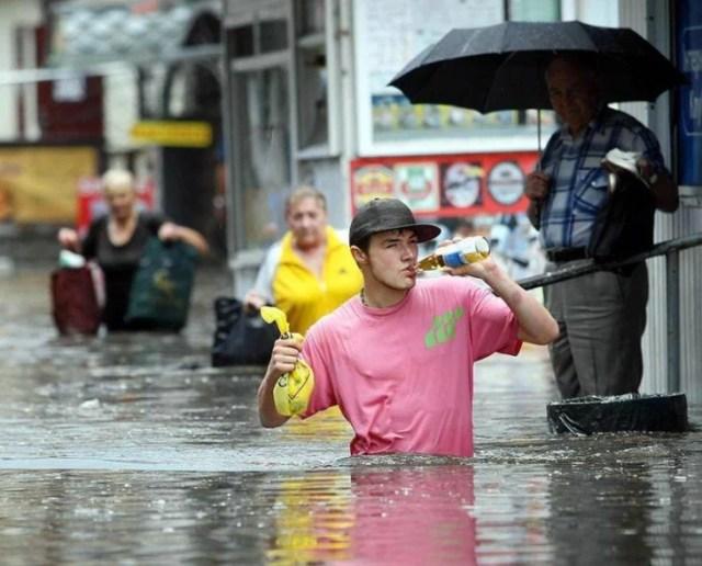 hombre tomando cerveza en medio de inundación