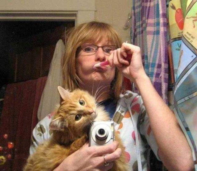 señora cepillando sus dientes, cuidando al gatito selfie