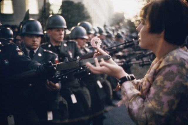 Manifestante coloca flores en armas
