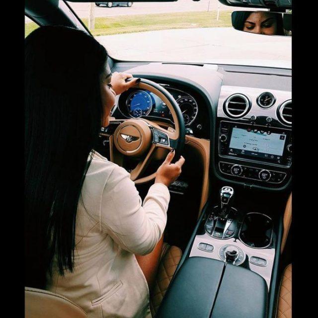 mujer manejando vehículo de lujo