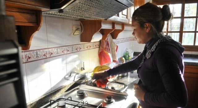 Una mujer, de perfil, limpia la cocina parada.