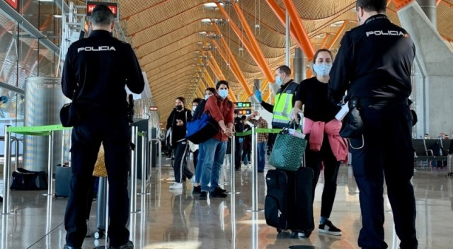Personas hacen fila en un aeropuerto, con barbijos puestos.