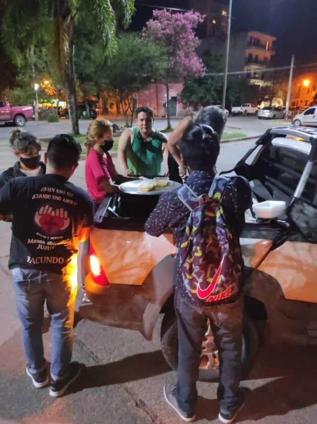 Voluntarios, alrededor de una olla, ayudan a personas en situación de calle.