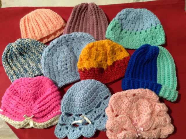Gorritos de lana de distintos colores apoyados en una mesa.
