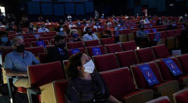 Sala de cine con personas, con distancia entre ellas y usando barbijos.