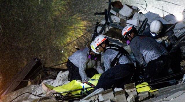 Tres rescatistas remueven escombros en busca de víctimas.
